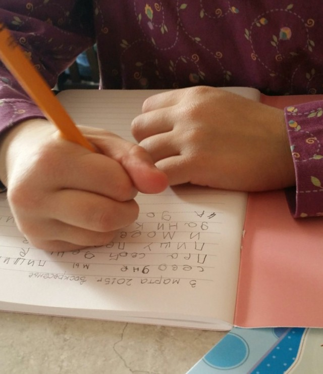little C. writes her first page in her new journal. She chose to write in Russian this time.